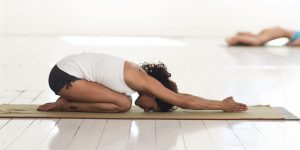 Yoga - Haltung des Kindes mit gestreckten Armen